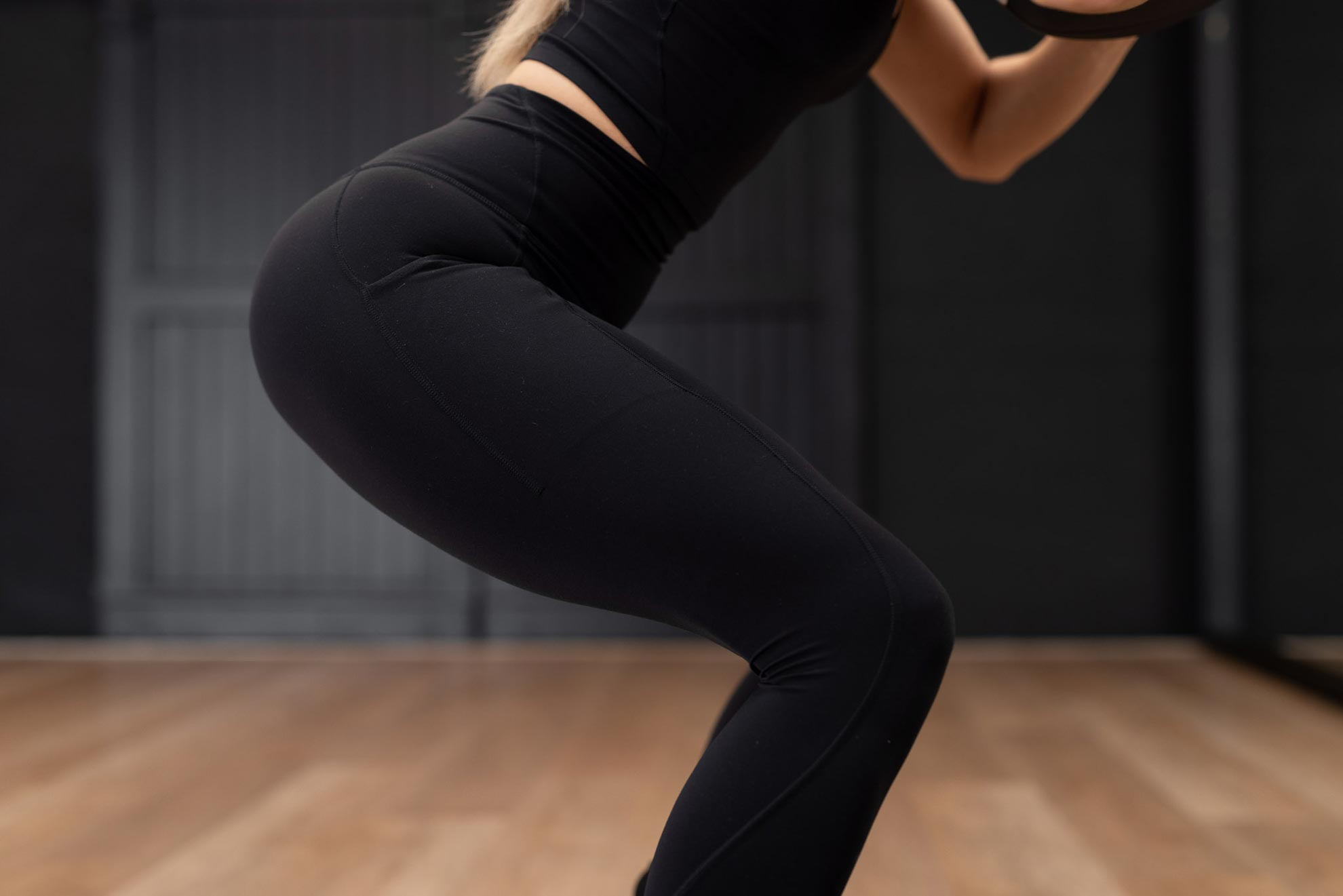 A cropped picture of a woman doing a squat in a pilates studio